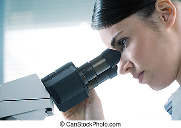 Female researcher using microscope close up - Young female...