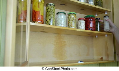 jars pickled food - hands take one after the other jars of...