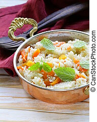 rice with vegetables cooked in Indian style in a copper pan