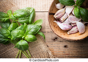 Spice - Bunch fresh basil on a wooden background Garlic...