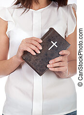 Bible - A young girl holding a bible in her hands
