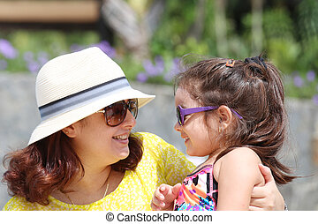 Portrait of mother and daughter outdoors looking each other in s