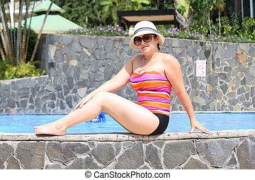 Beautiful woman posing in the pool