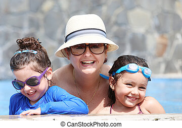 Happy mother with her kids in the pool