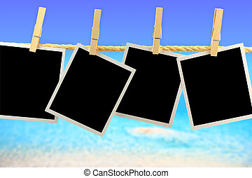 Photo frames hanging on a rope in front of the sea