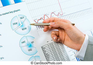 female hand pointing pen on financial charts