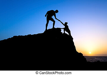 Man and woman help silhouette in mountains - Couple hiking...