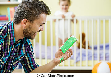 Father and daughter - Father holding damaged mobile phone...