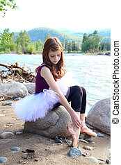 Young ballerina - Beautiful girl wearing a white tutu by the...