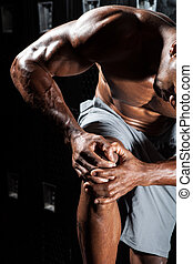 Knee Pain - Portrait of a muscle fitness man reaching for...