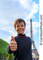Cheerful teenager shows thumb up near Eiffel Tower La Tour...