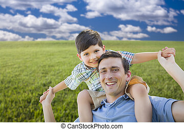 Mixed Race Father and Son Playing Piggyback on Grass Field
