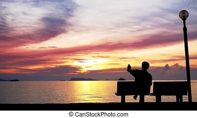 Man Sit on the Beach and Takes Picture of Beautiful Sunset.