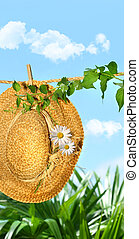 Summer straw hat with daisies on clothesline