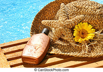 Summer straw hat with tanning lotion by the pool