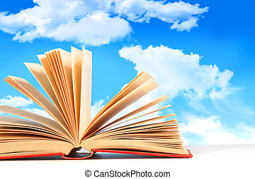Open book against a blue sky - Open book on white surface...