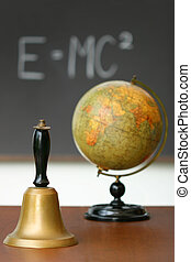 Old school bell on desk in front of chalkboard