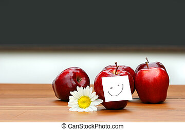 Delicious red apples on desk with blackboard