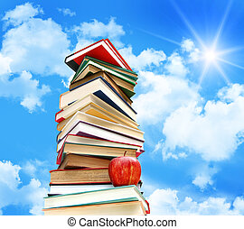 Pile of books and apple against blue sky with clouds