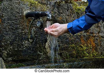 Person haelt Haende unters Wasser - Person erfrischt sich...