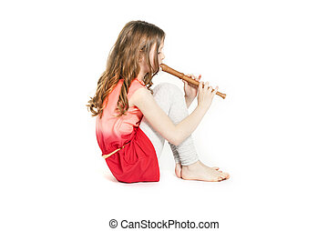 young girl sitting with soprano recorder and white...