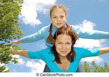 Happy smiling Mother and the daughter fly in sky