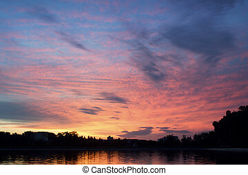 pink sunset - beautiful sun setting over calm city lake