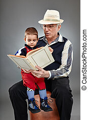 Grandpa reading fairytales to toddler - Grandfather reading...