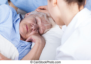 A nurse assists older woman - A nurse assists a sad older...