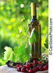 Bottle and glass of white wine and cherries