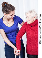 Mature lady practicing walking with nurse - Mature lady...