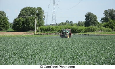 fertilizing tractor makes a turn a cereal field and continue...