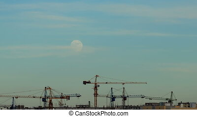 The moon over a building site - The moon in the sky over a...