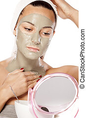 face mask - young beautiful woman applied a mask on her face