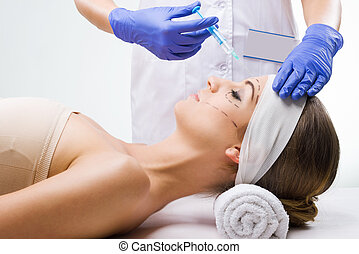 Beautiful woman lying in the clinic, a plastic surgeon in...