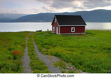 Rustic red cabin - Red wooden cabin on the shore in Nordic...