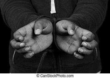 Slavery - Closeup view of someone\'s hands being tied...