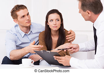 Discussing contract Thoughtful young couple sitting on the...