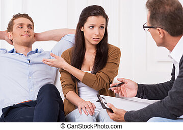 He is not taking me seriously! Frustrated young woman pointing her smiling husband while talking to psychiatrist