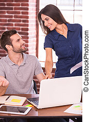 Helping out a colleague. Cheerful young man sitting at his working place and gesturing while beautiful woman standing close to him and smiling
