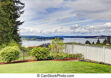 Fenced backyard with water view