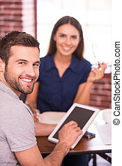 Young and creative colleagues. Two cheerful business people in casual wear sitting at the table together and looking at camera while man holding digital tablet