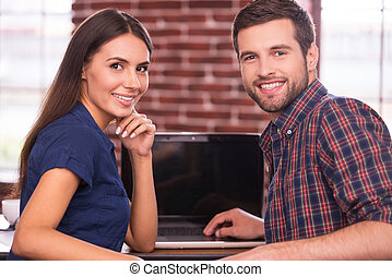 Confident cooperation. Cheerful young man and woman sitting at t