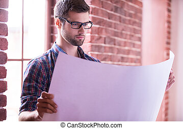 Architect examining blueprint. Confident young man in...