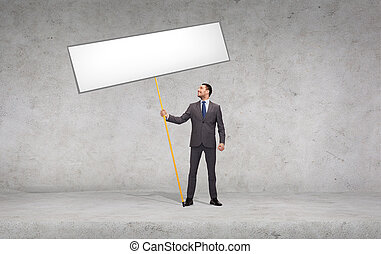 smiling businessman holding white blank board