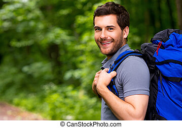 Handsome tourist. Handsome young man carrying backpack and...