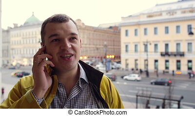 Young excited man talking on the phone outdoor