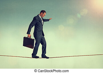 business balance - courageous businessman balancing on a...