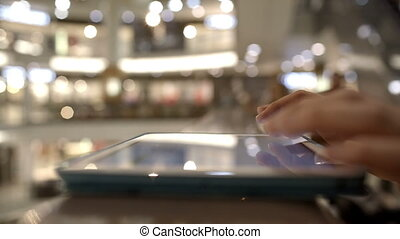 Woman using tab on handrails in shopping center - Close-up...