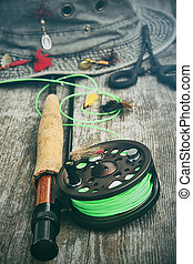 Fly fishing reel with old hat on bench - Fly fishing reel...